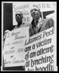 Freedom riders James Peck, head bandaged, with Henry Thomas, each wearing a placard, picketing outside the New York City Port Authority Trailways bus terminal